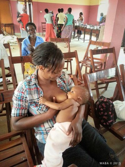John Musisi - Mother and baby at lunch breask during training for OVC caregivers